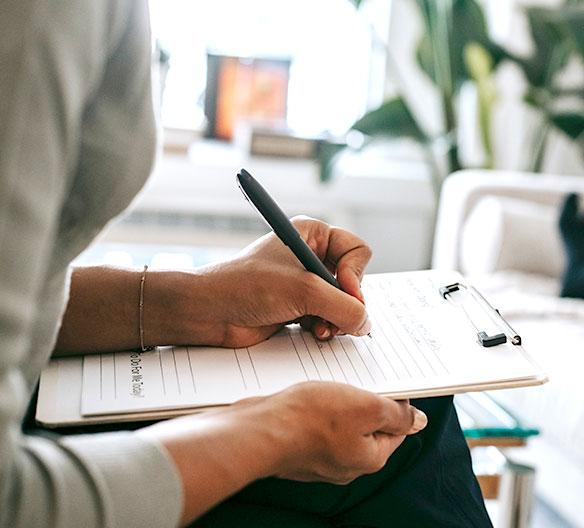 therapist writing on clipboard